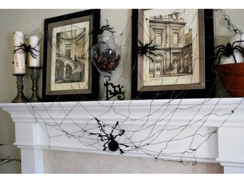 a vintage-inspired Halloween mantel with spiders, spiderwebs, candleholders and bold vintage photos