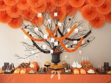 a black urn with black branches, with black yarn balls and black and orange garlands to decorate your dessert table for Halloween