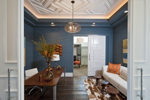 geometric molding on the ceiling and a matching sliding door add chic and style to the space
