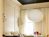 a single ceiling molding piece highlights the paper lamp that is hanging very low over the table