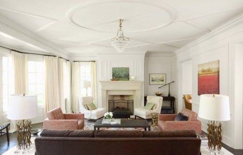 an elegant feel is give to the living room with ceiling molding, elegant lamps, a crystal chandelier