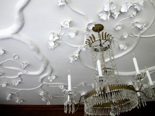 this molding imitates flowers and looks very natural, as if they are growing on the ceiling and a crystal chandelier adds to the space