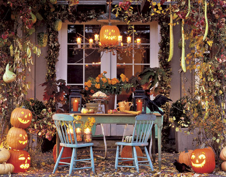 a bright classic Halloween terrace with lots of carved pumpkins, leaves, gourds, faux birds and Jack o lanterns