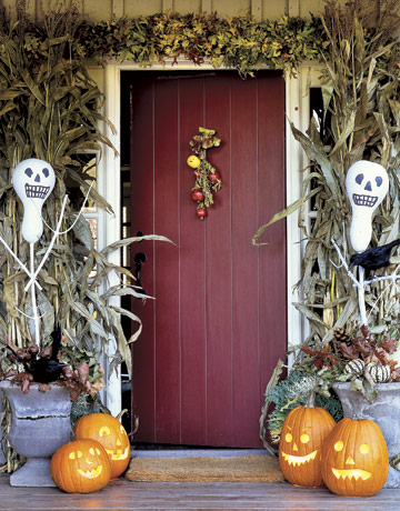 classic Halloween front porch decorating with Jack o lanterns, corn husks, ghosts, fall leaves and pumpkins is chic