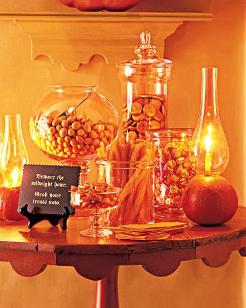 a bright orange candy table for Halloween, with lights, candles and a black card