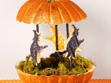 a glitter orange pumpkin with moss and paper witches is a cool decoration for the fall and Halloween