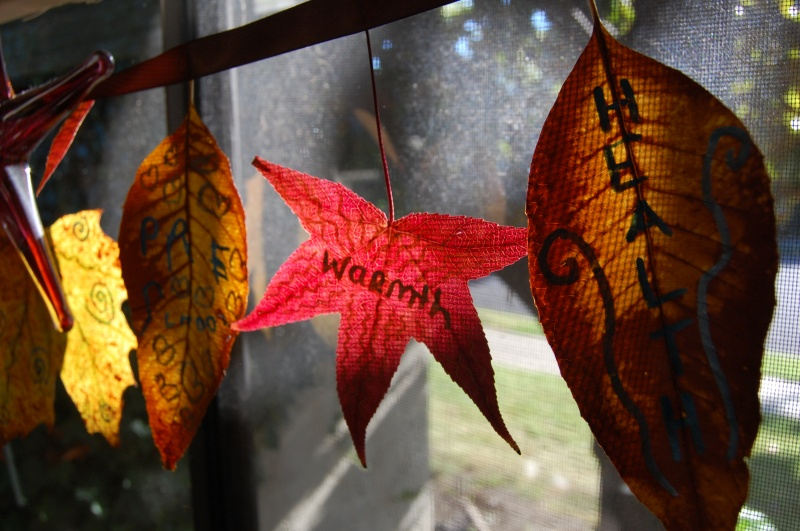 a garland of fabric and just dried leaves with wishes is a great all natural decoration for Thanksgiving, both indoors and outdoors