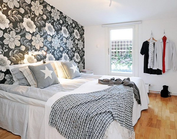 a white bedroom spruced up with a dark floral accent wall makes it more interesting and bold