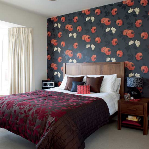 an exquisite bedroom with a dark floral accent wall and a dark blanket on the bed plus matching pillows