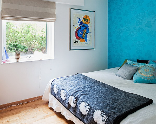 a bedroom spruced up with a super bright and colorful wallpaper accent wall that takes over the whole room