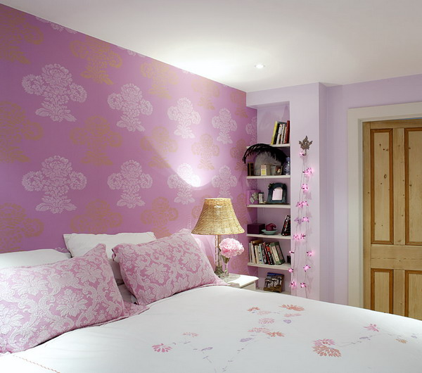 a girlish bedroom with a pink floral accent wall and matching bedding is a cool and romantic space