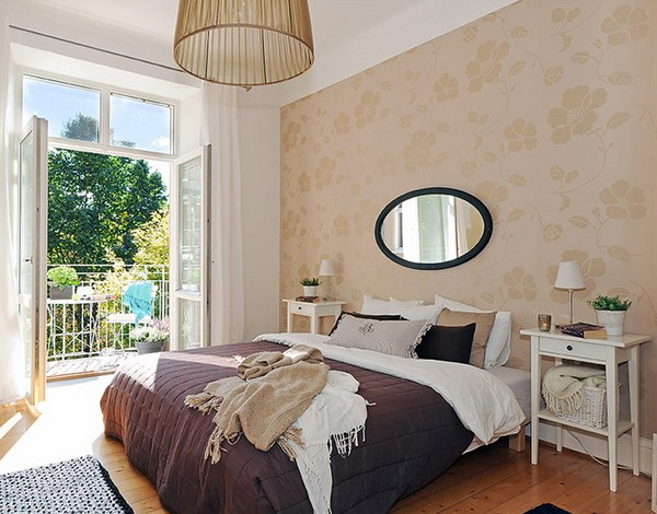 a neutral bedroom with a tan printed accent wall that subtly adds pattern and color to the space