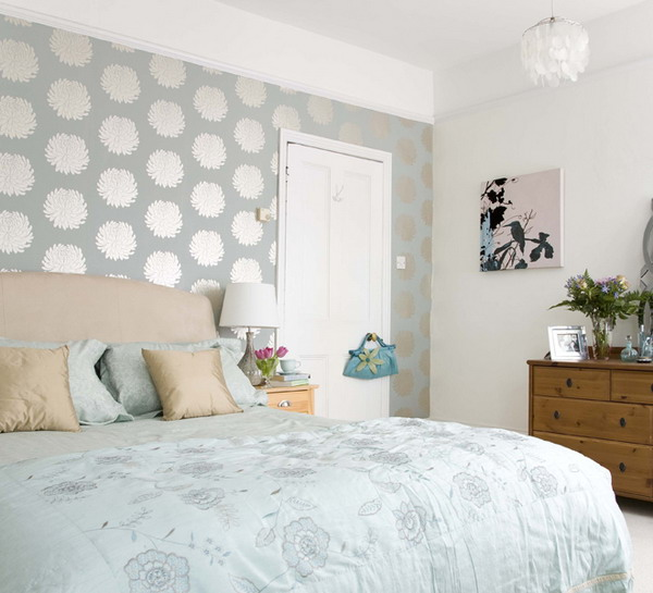 a pastel bedroom with a light green printed wall for a slight touch of color and pattern
