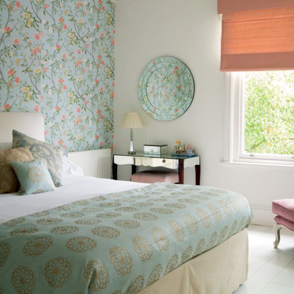 a grene floral accent wall, matching bedding and a printed plate on the wall for subtle and soft touches