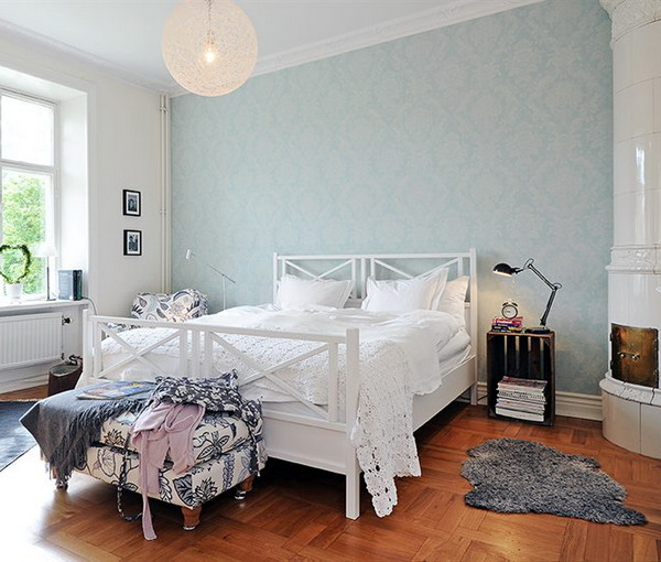 a neutral bedroom with a pastel blue printed wall that gives a light touch of color and makes the room interesting