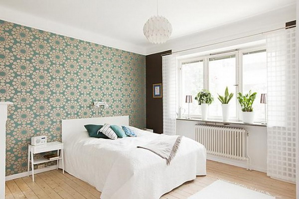a white bedroom with a bright printed accent wall that takes over the whole space and gives tone to it