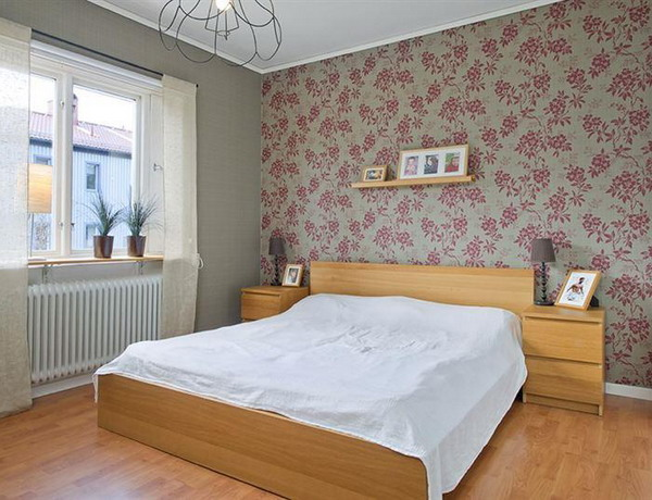a grey bedroom with a grey and pink floral accent wall that gives a soft feel to the space