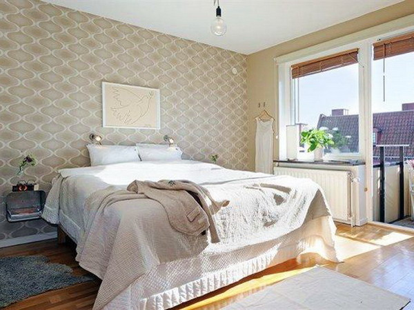 a neutral bedroom with a printed accent wall that subtly adds interest and chic to the room without being too much