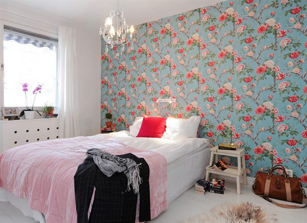 a colorful bedroom with a bright floral accent wall in blue and reds spruces up the whole room and makes it outstanding