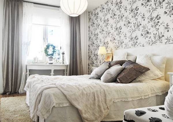 a monochromatic room with a botanical print headboard wall that adds pattern to the space