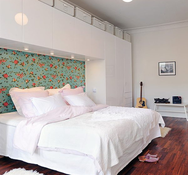 a white minimalist bedroom with a bright floral accent wall and lights over it to infuse the space with color and pattern