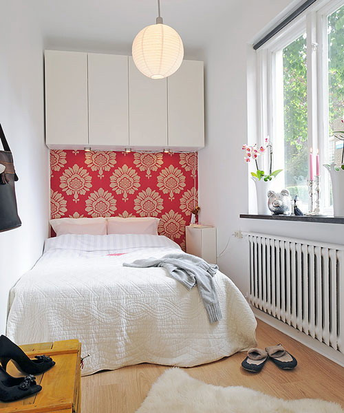 a small white bedroom refreshed with a single bright spot   a coral patterned accent wall behind the bed
