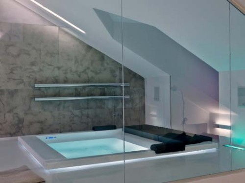an ultra-modern attic bathroom with skylights, some neon light, a large bathtub for pure relaxation