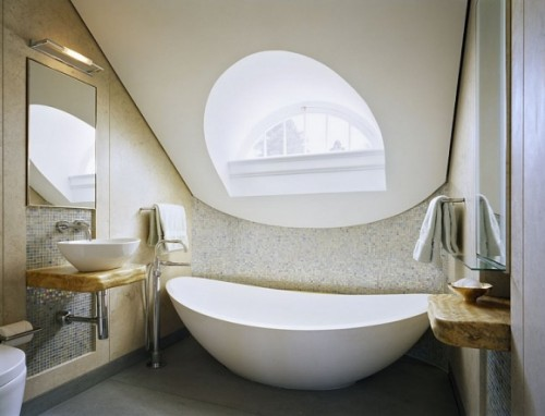 a neutral attic bathroom done with a large attic detail with a round window, an oval tub, floating shelves and vanities