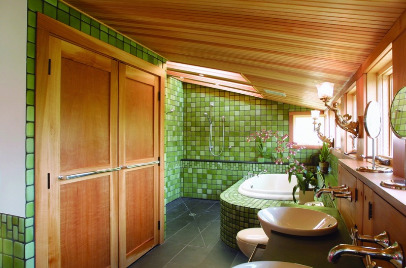 a green bathroom with lots of natural wood