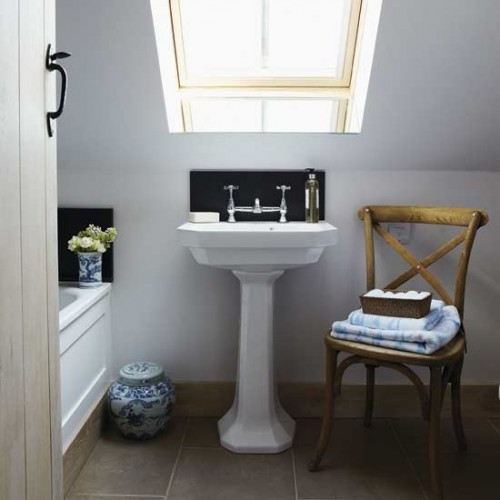 a small and cozy attic bathroom with a skylight, a bathtub, a chair and a free-standing sink is a functional space
