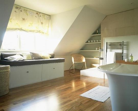 a large neutral bathroom with a window, a window seat with storage, shelves, chairs and a vintage inspired tub