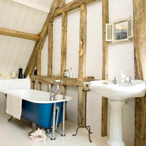 a cozy attic bathroom design with wooden beams, a blue vintage tub, a small window and a free-standing bathtub