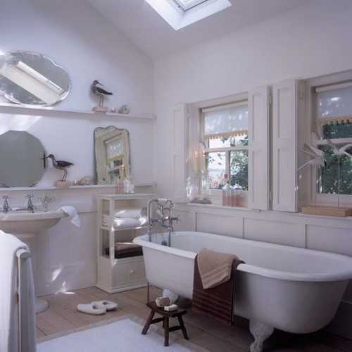 a neutral vintage-inspired attic bathroom with windows and skylights, with a free-standing tub and sink, with some mirrors