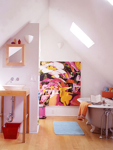 a small and colorful attic bathroom with a skylight, a vintage tub, a colorful artwork and a wooden vanity