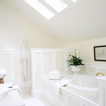 a neutral attic bathroom done in tan and white, with skylights, a shower space, a built in tub and some blooms