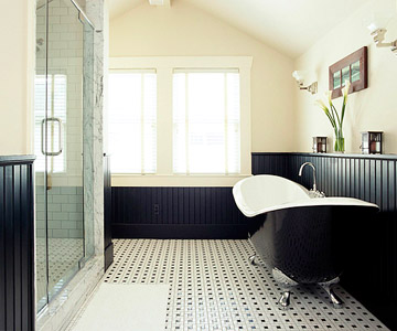 an elegant monochromatic bathroom with black paneling, a free-standing tub, a window, a shower enclosed in glass