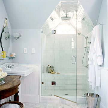 a tiny white attic bathroom with a skylight, a small shower space, a sink and vintage decor here and there