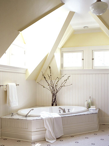 a neutral rustic attic bathroom with skylights and windows, with paneling, tiles and a built-in bathtub