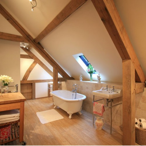 a warm and cozy attic rustic bathroom with wooden beams, neutral tiles, a free-standing tub and sink plus a cool wooden vanity