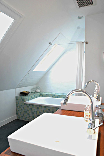 a small attic bathroom with white walls, a built-in tub clad with green tiles, a stained vanity with two sinks