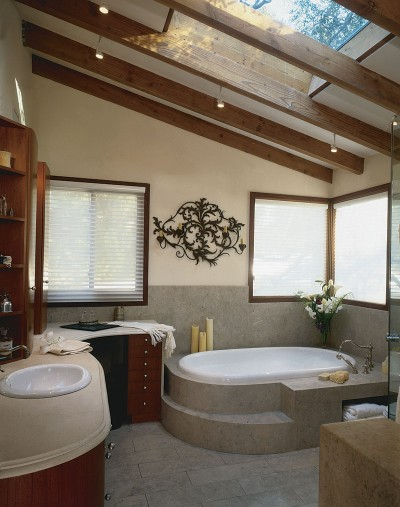 a rustic attic bathroom with wooden beams and skylights, with a built-in tub and stained wooden furniture and windows
