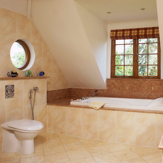 a warm attic bathroom clad with tiles in tan and brown, with several windows looks very inviting and cool