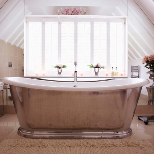 a vintage-inspired attic bathroom with tan tiles, a metal clad bathtub and a large window for views and much light
