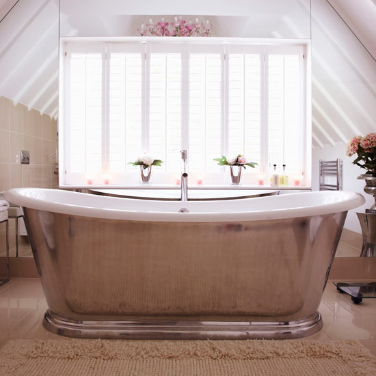 a vintage inspired attic bathroom with tan tiles, a metal clad bathtub and a large window for views and much light