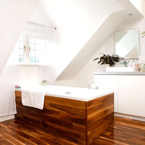 a modern attic bathroom with white walls, a window, a wooden floor and a wood clad bathtub