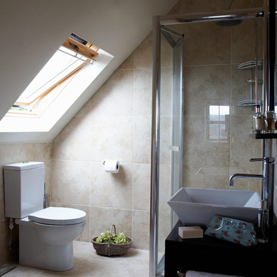 a small contemporary bathroom with a window, a shower space, a sink on a vanity and neutral tan tiles all over