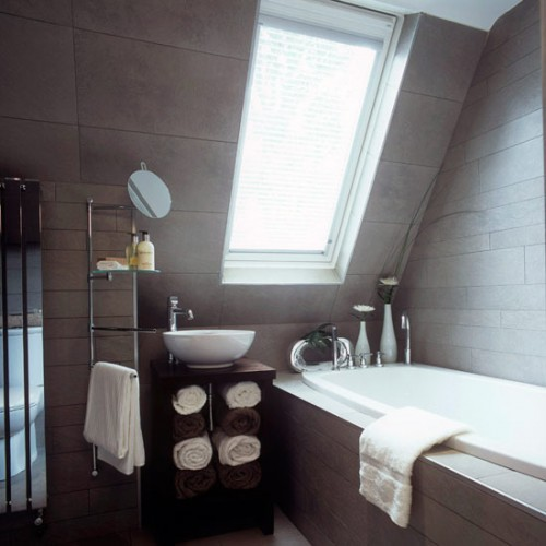 a small contemporary attic bathroom clad with neutral tiles, a large skylight, a bathtub cla with tiles, too