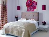 fuchsia-colored hanging lamps over the bed and a matching artwork make the space bolder and cooler