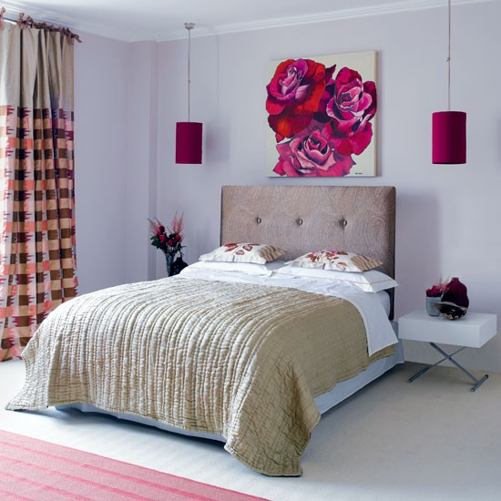 fuchsia colored hanging lamps over the bed and a matching artwork make the space bolder and cooler
