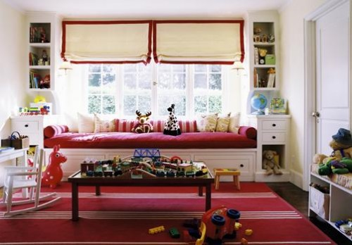 a bright kid's space with a red daybed with pillows and toys and bookshelves built-in on each side of the bed